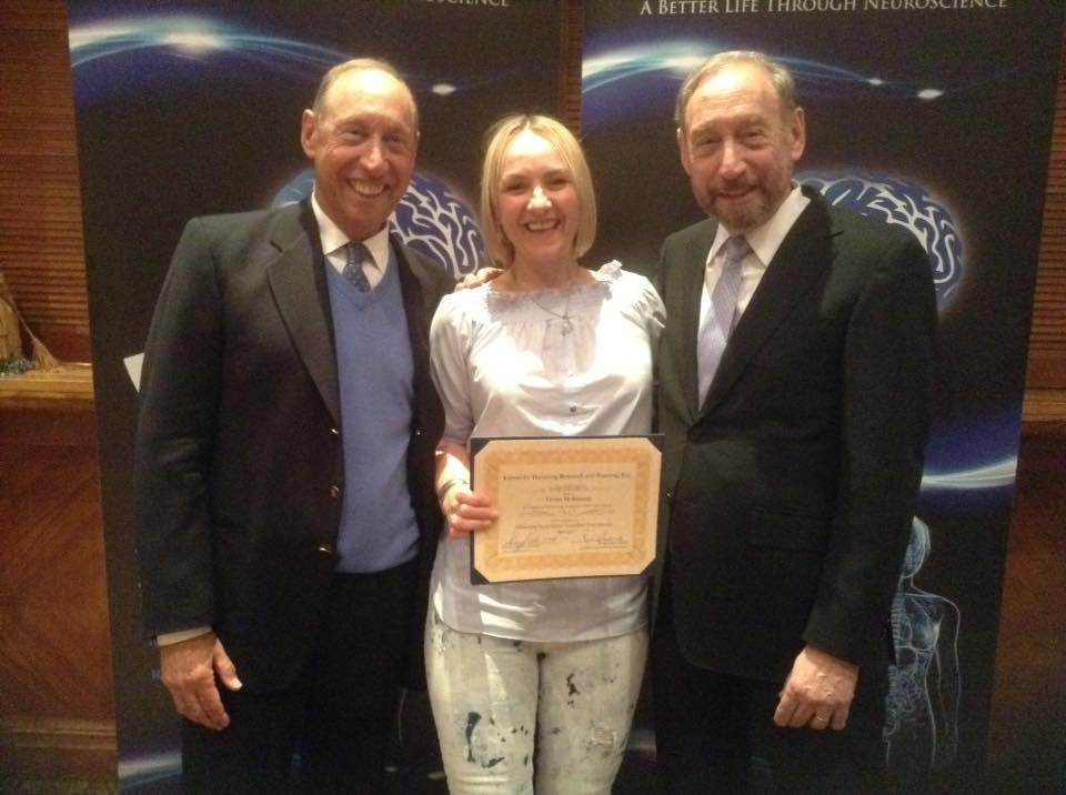 Image of Vivian receiving her certificate from Dr's Ron and Steve Ruden